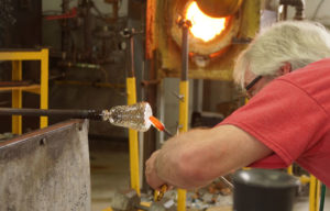 Setting up to transfer the work to the punty or pontil rod - glass blower Mark Armstrong of Armstrong Glassworks in Wellington, ON