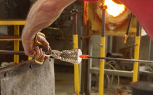 Cutting work off the blow pipe - glass blower Mark Armstrong of Armstrong Glassworks in Wellington, ON
